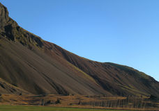 Dark brown mountain range against the blue sky, Iceland Stock Images