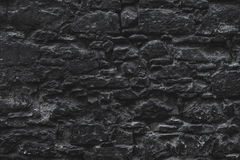 Dark brown old medieval natural stone wall. Texture, background or wallpaper. Royalty Free Stock Photo