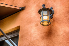 Dark brown outside lighting fixture against a stone wall. Royalty Free Stock Photography