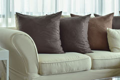 Dark brown pillows setting on beige color sofa Royalty Free Stock Photography