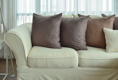 Dark brown pillows setting on beige color sofa Royalty Free Stock Photo