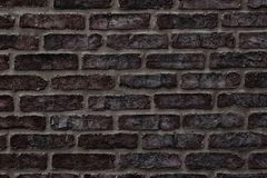 Dark brown rough brick wall close-up texture for background. Dark brown brick wall close-up texture. Rough aged brickwork. Grungy masonry background Stock Photo