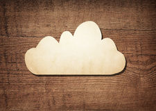 Dark brown scratched wooden board, wood texture with paper cloud symbol Royalty Free Stock Photo