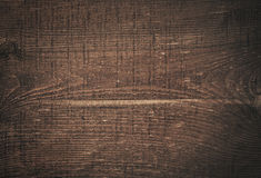 Dark brown scratched wooden cutting board. Wood Royalty Free Stock Image