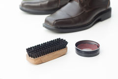 Dark brown shoe with shoe polish and brush shoe Stock Image