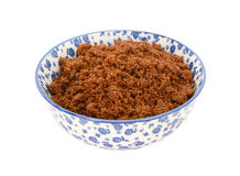 Dark brown soft sugar in a blue and white china bowl Royalty Free Stock Photo