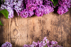 Dark brown wood table with frame on bunch of lilac flowers. Empty template for text stock photos