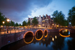Dark canals Amsterdam. Beautiful cityscape of the famous canals of Amsterdam, the Netherlands, at night with bridges at the Emperor`s canal keizersgracht and Stock Images