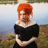 Dark carnival attire. Enigmatical witch woman with pale skin and red hair in black mystical gown and renaissance bracelet on hand stock photos