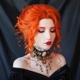 Dark carnival attire. Redhead woman witch with pale skin in a black victorian dress and a necklace on neck. Victorian redhead girl. Witch with red lips. Gothic royalty free stock photos
