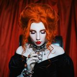 Dark carnival attire. Scary witchcraft. Mystical woman sorceress with pale skin in a black victorian dress. Redhead model with red. Lips. Mystical look. Outfit royalty free stock images