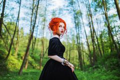 Dark carnival attire. Witch woman with pale skin and red hair in black mystical gown and renaissance bracelet on hand pronounces s stock images