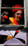 Dark Carnival Clowns. Looking Sinister And Scary Peer Through A Haunted House Window At A Chilling Halloween Party Stock Photos