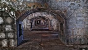 Dark casemates inside the old fort. Archs made of stone stretch deep into the fortress Royalty Free Stock Photo