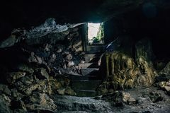 Dark cave with steps of staircase and light from entrance. Toned Royalty Free Stock Image