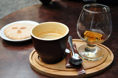 Dark ceramic cup of coffee, glass of cognac and italian almond cantuccini cookie on a white plate on an old wooden table at a cafe Royalty Free Stock Photos