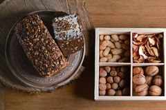 Dark cereal bread with sunflower seeds, several kinds of nuts in a box, concept of healthy eating, on a wooden background on a stu. Mp, set Royalty Free Stock Images