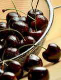 Dark cherries in mesh sieve on wooden table Royalty Free Stock Image