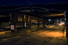 Dark Chicago city alley industrial train bridge at night. Dark Chicago city alley industrial train bridge underpass at night royalty free stock photography