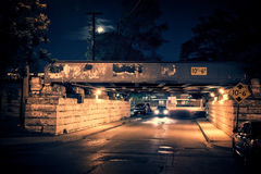 Dark Chicago city street landscape with train bridge, alley, moo Stock Image