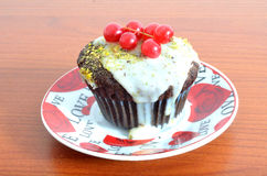 Dark chocolat muffin with white topping and red currant. Dark chocolate muffin with white chocolate  topping chipped pistachio and red currant, love saucer Stock Photos