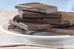 Dark chocolate. Stack of broken dark chocolate bar in glass saucer on beige napkin against blue background Royalty Free Stock Photography