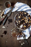 Dark chocolate and almonds cake on wooden table with cloth and utensils Stock Image