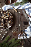 Dark chocolate and almonds cake on wooden table with pine branches and cloth and utensils Stock Photo