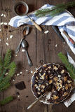 Dark chocolate and almonds cake on wooden table with pine branches and cloth and utensils Royalty Free Stock Image