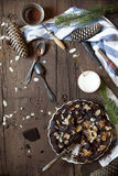 Dark chocolate and almonds cake on wooden table with pine branches and cones, cloth and utensils Stock Photos