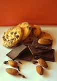 Dark chocolate, almonds and cookies with chocolate chips on red background Royalty Free Stock Photo