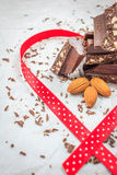 Dark chocolate and almonds decorated with red ribbon. On white paper Royalty Free Stock Images