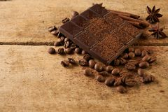 Dark chocolate arabica coffee beans cinnamon. A large bar of dark chocolate arabica coffee beans cinnamon and anise on old wooden rustic background with copy Royalty Free Stock Images