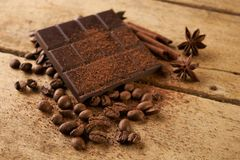 Dark chocolate arabica coffee beans cinnamon. A large bar of dark chocolate arabica coffee beans cinnamon and anise on old wooden rustic background with copy Royalty Free Stock Photography