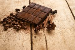 Dark chocolate arabica coffee beans cinnamon. A large bar of dark chocolate arabica coffee beans cinnamon and anise on old wooden rustic background with copy Stock Images