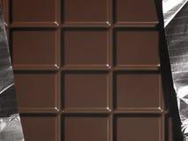 Dark chocolate bar with aluminium foil Stock Image