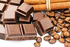 Dark chocolate bar, cubes, cinnamon sticks and coffee beans isolated on white background. Royalty Free Stock Image