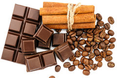 Dark chocolate bar, cubes, cinnamon sticks and coffee beans isolated on white background, top view. Royalty Free Stock Images