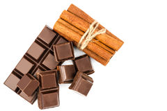 Dark chocolate bar, cubes and cinnamon sticks isolated on white background, top view. Stock Photography