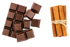 Dark chocolate bar, cubes and cinnamon sticks isolated on white background, top view. Stock Image