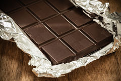 Dark chocolate bar in opened foil wrapping. Royalty Free Stock Photos