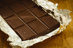 Dark chocolate bar in opened foil wrapping. Stock Photo