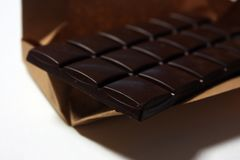 Dark chocolate bar in pack backround. Tasty and healthy food stock image