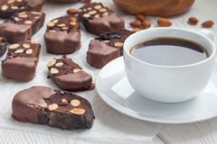 Dark chocolate biscotti cookies with almonds, covered with melted chocolate, and cup of coffee, horizontal royalty free stock photography