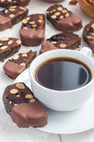Dark chocolate biscotti cookies with almonds, covered with melted chocolate, and cup of coffee, vertical. Homemade dark chocolate biscotti cookies with almonds stock images