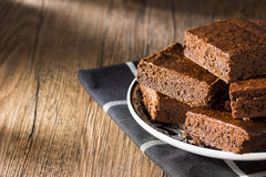 Dark Chocolate Brownies on Rustic Wood. A stack of freshly baked fudgy chocolate brownies sit on top of a plate on a black and white plaid napkin waiting for Stock Images