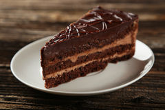 Dark chocolate cake on brown wooden background. Royalty Free Stock Photography