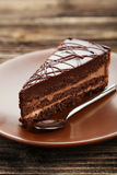Dark chocolate cake on brown wooden background. Royalty Free Stock Photos