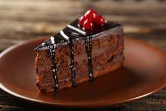 Dark chocolate cake on brown wooden background. Stock Photos