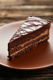 Dark chocolate cake on the brown wooden background Royalty Free Stock Images